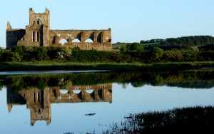 A ruined abbey against a blue sky reflected in a river in the foreground