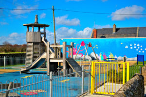 A childrens playground with a wall mural in the background