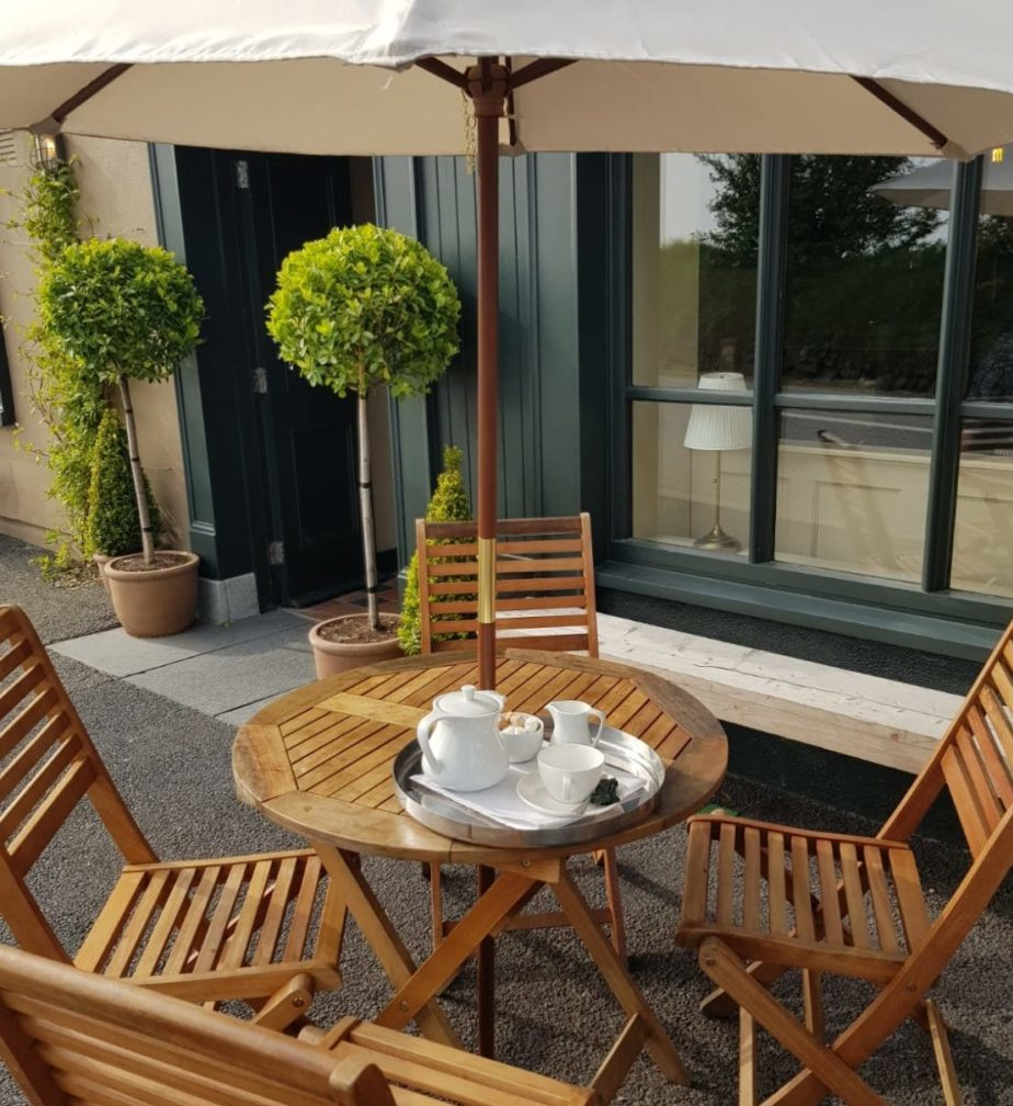 Wooden table and chairs under parasol outside Foleys Bar